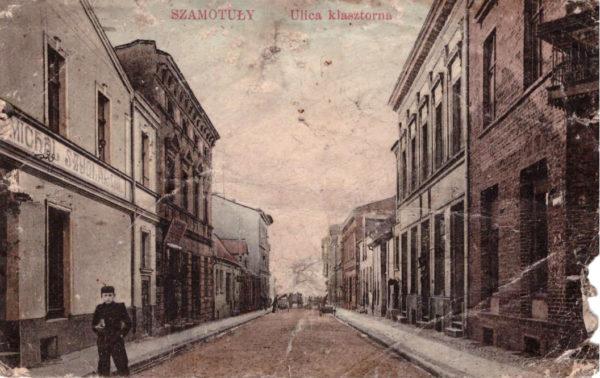 Pocztówka po 1905 przed 1914 Fragment ulicy Klasztornej 9obecnie Dworcowa – po lewej sklep Michała Szydlarskiego